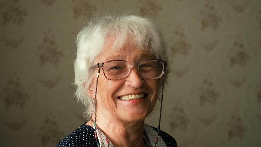 Portrait of a happy grandmother. Happy elderly woman with eyeglasses smiling and looking into a camera. Senior people portrait authentic video. Stay home concept, isolation period for retired people