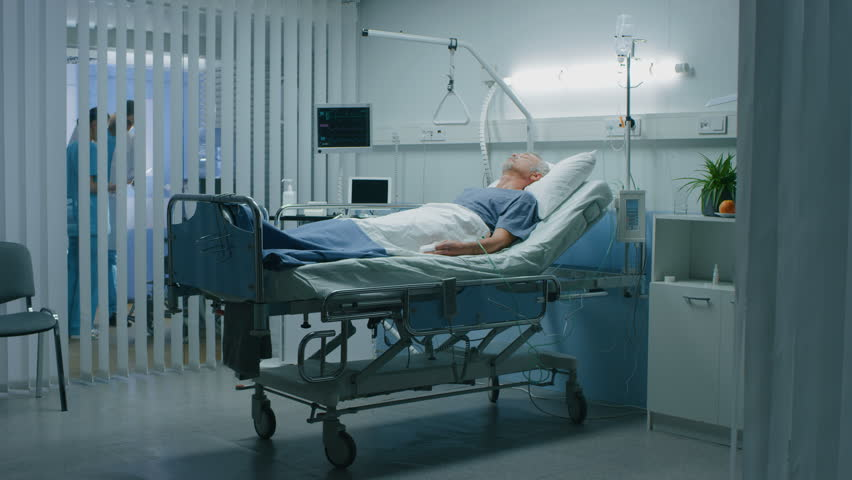 In the Hospital Senior Patient Rests, Lying on the Bed. Recovering Man Sleeping in the Modern Hospital Ward. Shot on RED EPIC-W 8K Helium Cinema Camera.