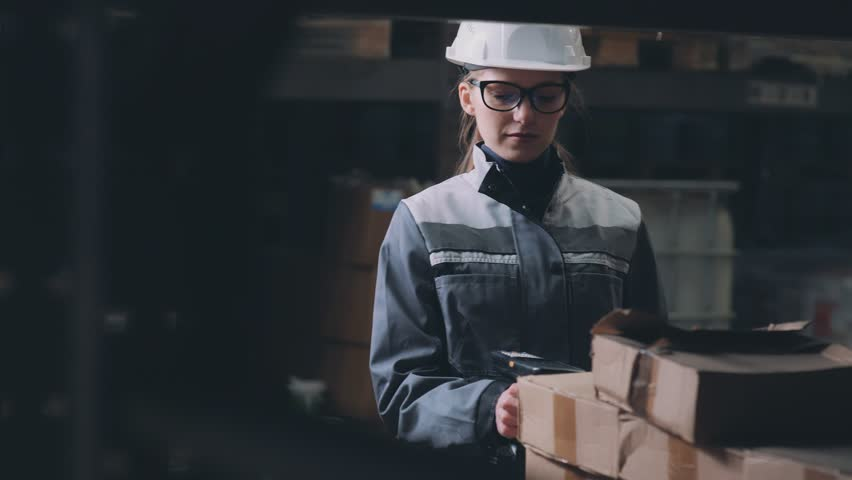 A woman in the warehouse scans the goods with a special reader. Scan bar code. A young woman in a warehouse in a white helmet and uniform scans the goods. Logistic warehouse.