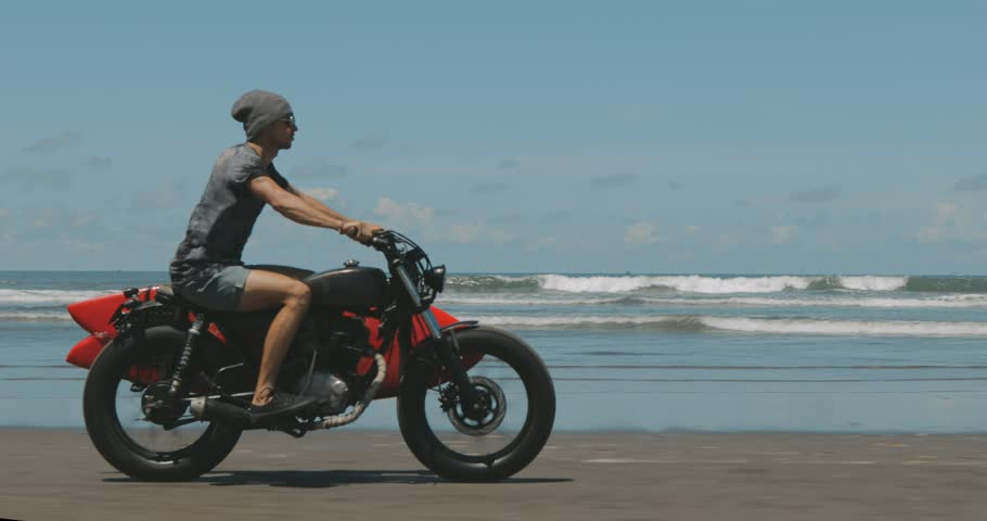 Handsome man biker surfer driving his black motorbike cafe racer with red surfboard shortboard on the beach along the ocean at sunny day. 4k video shooting by handheld gimbal | Shutterstock HD Video #1009731614