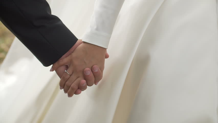 Close-up shot of the newlywed cou ple is softly holdign hands while walking. No face. #1009731773