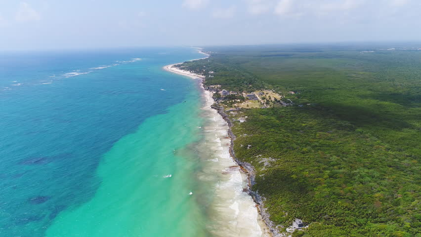 Aerial view of ruins in coastal Mayan city of Tulum, lush jungle, beach and crystal clear waters of Caribbean Sea - Yucatan Peninsula, Mexico from above, 4k UHD