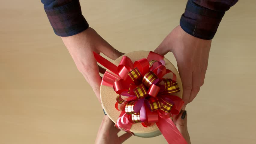 Men's hands give a box with a gift to a woman. Top view.   Shutterstock HD Video #1009741523