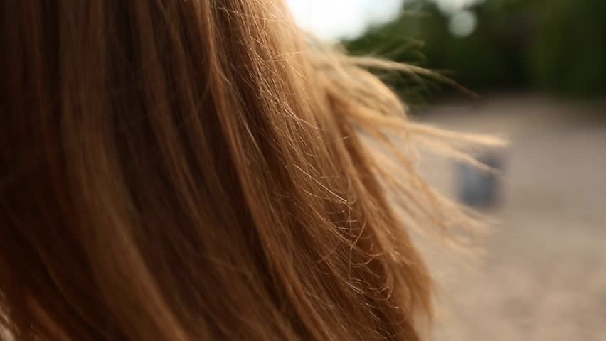 Close back view of red woman hair tender movement in the air in slow motion. Redhaired woman walking on sandy beach. Wind blows airy ginger hair shining in sun on sunset. Macro video.