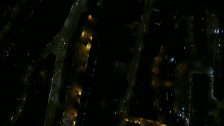 Aerial overhead rooftop view at night London suburban neighborhood street lights residential housing and commuter traffic England UK RED WEAPON
