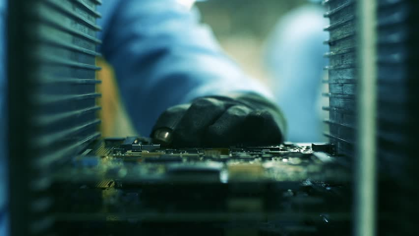 Assembly Line Worker holding an Electronic Circuit Board in a Computer Factory. Close-Up. Zoom In.