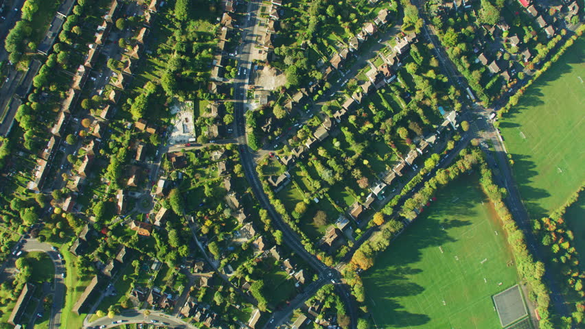 Aerial overhead view at sunrise London suburb community housing rooftops and vehicle travel on residential streets England UK RED WEAPON
