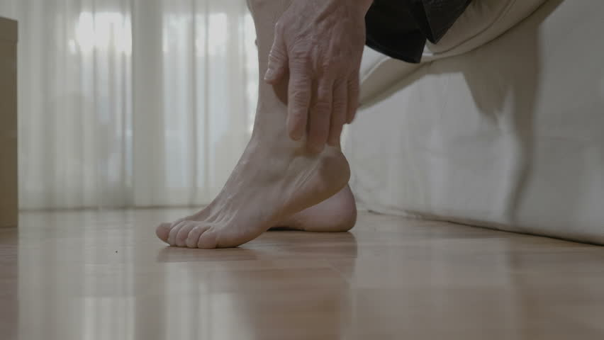 Patient mature man with arthritis sitting on bed and rubbing his ankle and foot relieving the ache