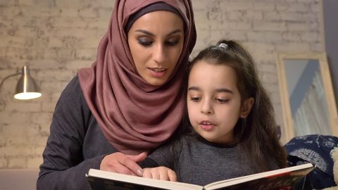 Young woman in hijab sits on sofa with her daughter and teaches her how to read, book, happy family concept, close up, home comfort in the background 50 fps