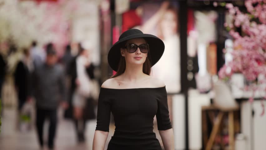 A young elegant rich girl in black dress and hat walks along the pedestrian shopping Mall street past the show rooms and boutiques. Slow motion