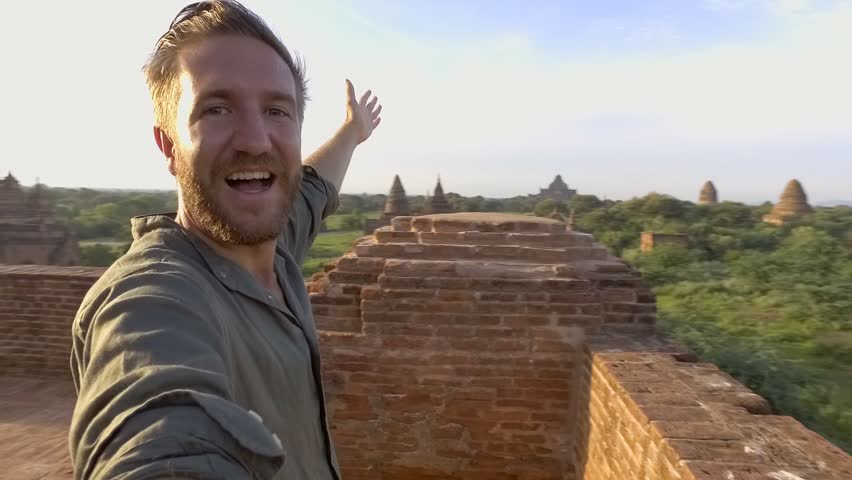 360 degree selfie, man takes a selfie point of view turning 360 degrees with camera. Young man traveller taking selfies on top on ancient Buddhist temple in Bagan Myanmar.
