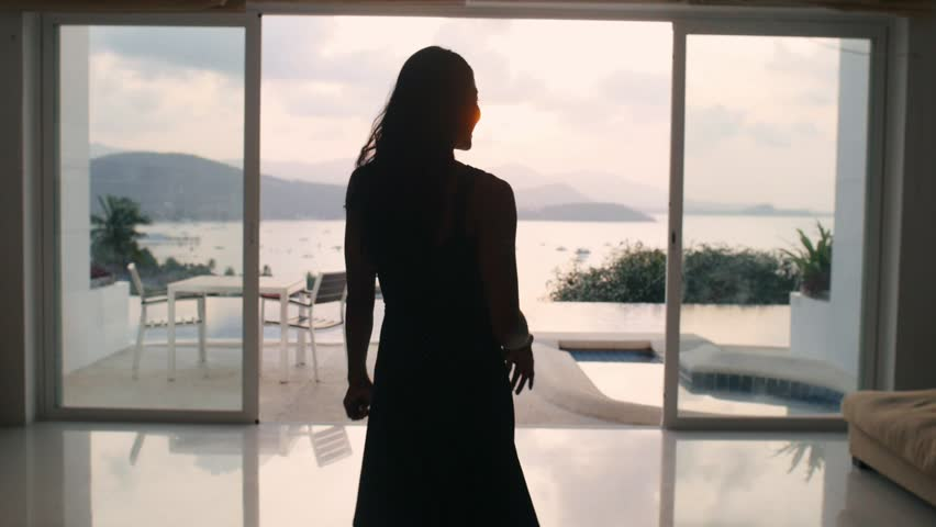 Smiling asian woman gesturing follow me and coming to outdoor terrace with infinity pool and showing panoramic view on sea landscape on luxury villa
