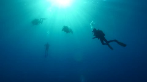 scuba diver under sun beams and light underwater sun shine