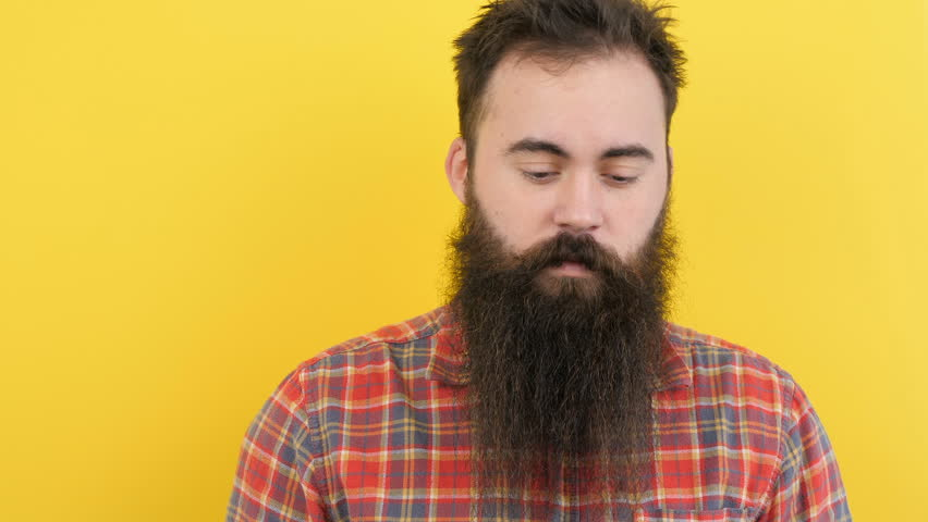 Hipster with long beard on yellow background looks at the camera then touches his beard. At the end of the clip he is smiling to the camera. Available in 4K resolution | Shutterstock HD Video #1009808123