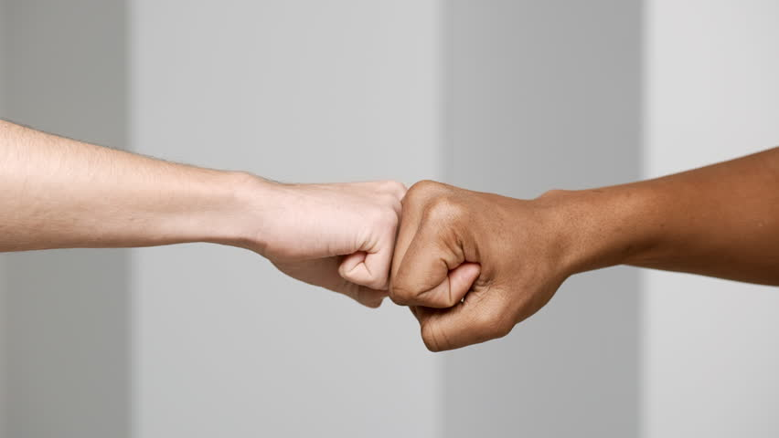 Hands gesture of two multiethnic men bumping fists closeup, isolated over white background in slow motion, friendship and greeting concept #1009808213