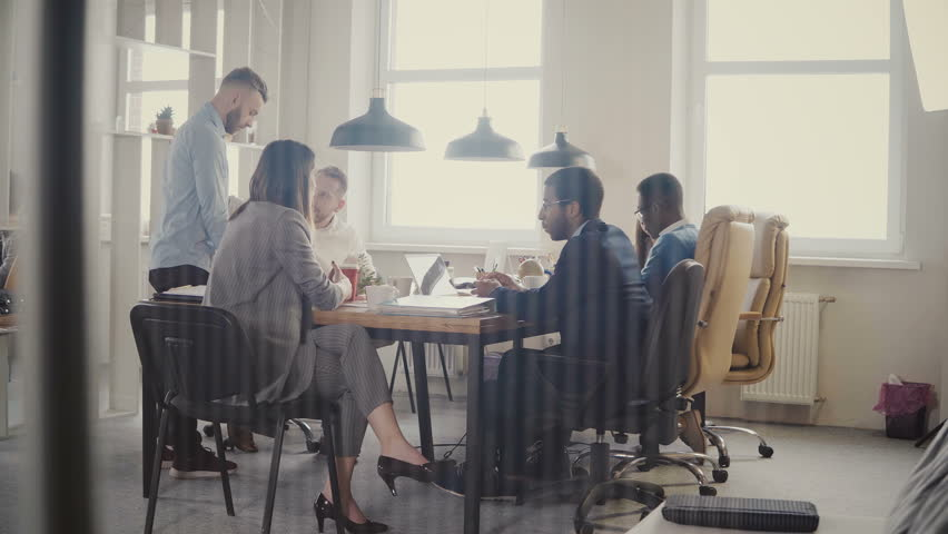 Dolly shot of teamwork at loft modern office table. Multiethnic business people cooperate, discuss market at meeting 4K. #1009818305