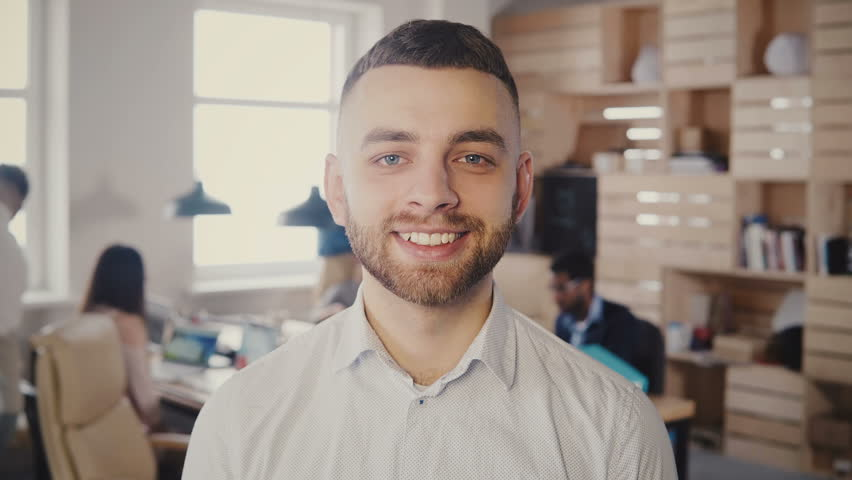 Portrait of young happy Caucasian businessman posing at busy office. Handsome male creative worker looking at camera 4K. | Shutterstock HD Video #1009818317