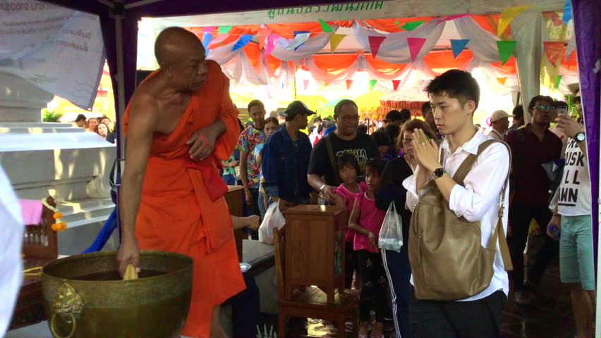 BANGKOK, THAILAND - April 2018 : People and Tourist pay respect to the monk and receive blessing from monk by sprinkle the holy water during Songkran Festival (Thai New Year) at Wat Pho Temple.