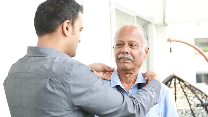 Closeup portrait, young guy helping older man to tie full windsor knot, isolated outdoors outside background