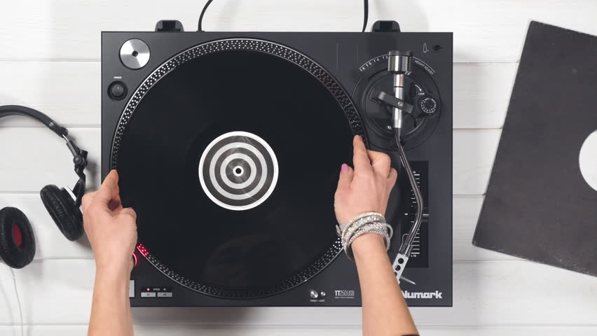 Varna, Bulgaria - April 2018, retro turntable Numark: top view of music player DJ girl who puts black vinyl plate, stylus with needle, takes black headphones her hands. Disco Styles 60s, 70s 80s