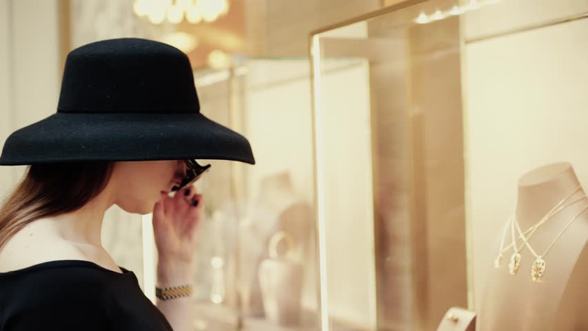 A beautiful young stylish lady in a hat and sunglasses approaches the shop window of a boutique and looks at goods with interest. Luxury jewelry store | Shutterstock HD Video #1009843748