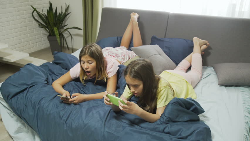 friendly relaxed young teenage girls chatting and browsing smartphone on bed at leisure time. modern digital device and gadgets addiction. #1009844735