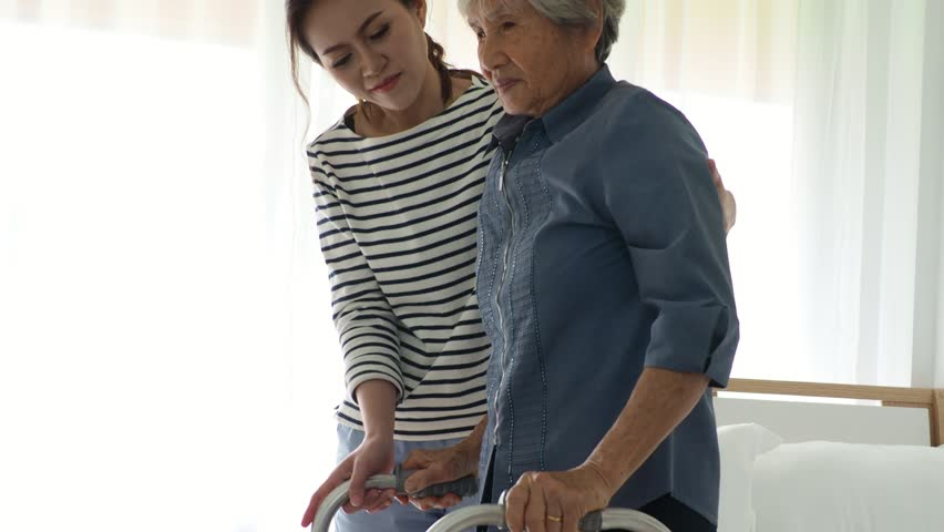 Young woman helping senior man to stand up with walker at home    Shutterstock HD Video #1009848182
