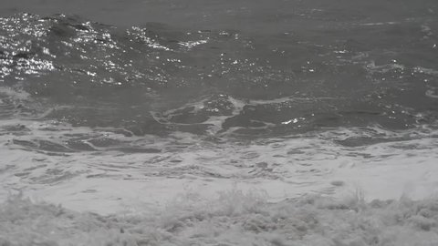 the stormy sea with high waves and gusts of wind hits the beach, raising splashes and foams
