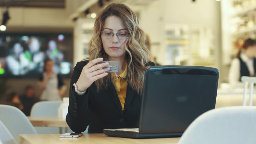 Young woman pays for purchase on the Internet by credit card | Shutterstock HD Video #1009861802