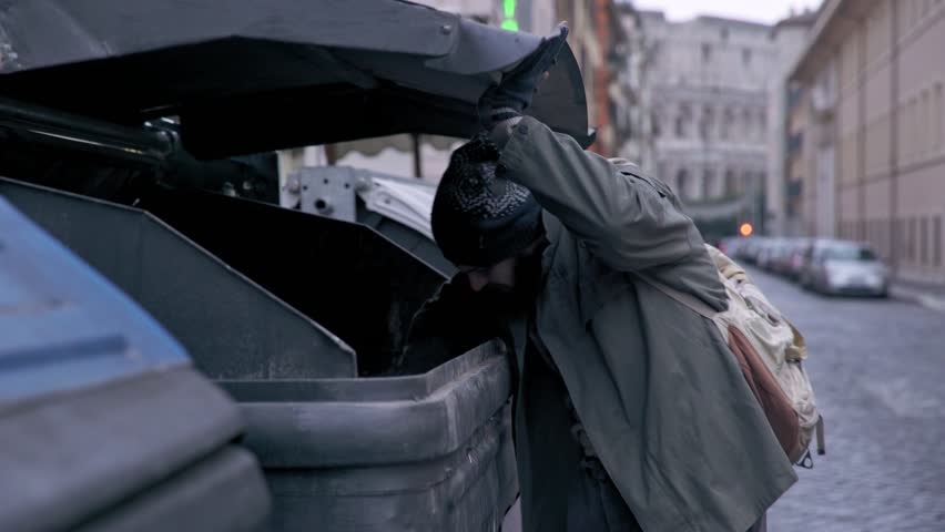 Hunger, misery, poverty-bum rummages in the dumpster in the street | Shutterstock HD Video #1009868426