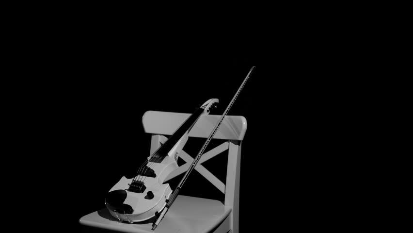 white violin on a white chair on a black background