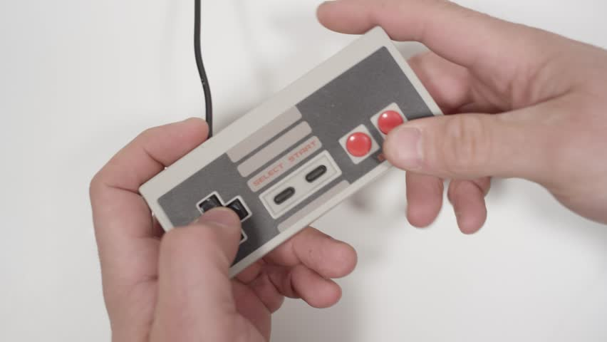 Retro video game controller on white background with hands playing mashing buttons