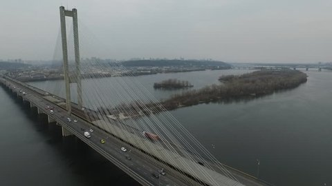 Aerial photography of road traffic through the railway bridge Kiev against the backdrop of the city of Kiev, bridge over the Dnieper river, view along the bridge, aerial separation from the bridge