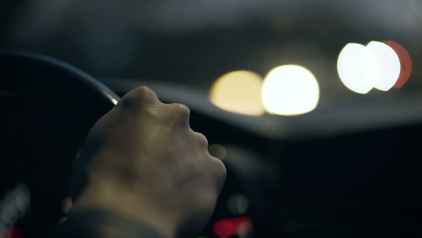 The driver's hand on the steering wheel against the background of the night road and the glare of passing cars. Close-up. 4K