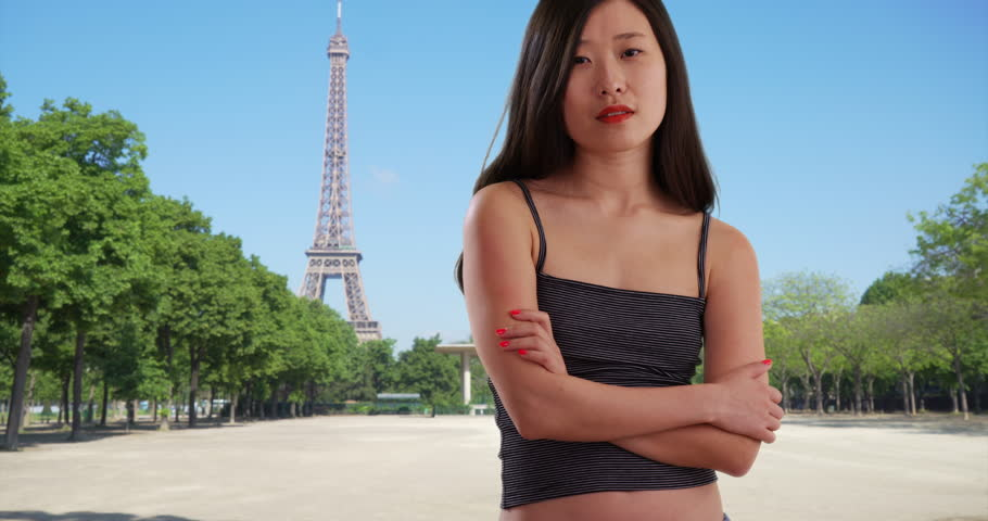 Happy millennial woman smiling for camera with arms crossed in Paris France. Close up of young Asian female with somber expression by Eiffel Tower in Europe. 4k | Shutterstock HD Video #1009888361