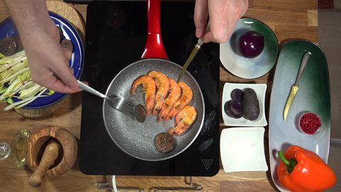 Top view food preparation Shrimp and violet potatoes to the pan on the stove with induction