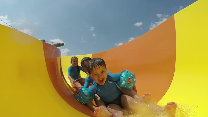 Funny little boys and girls roll with yellow water slides