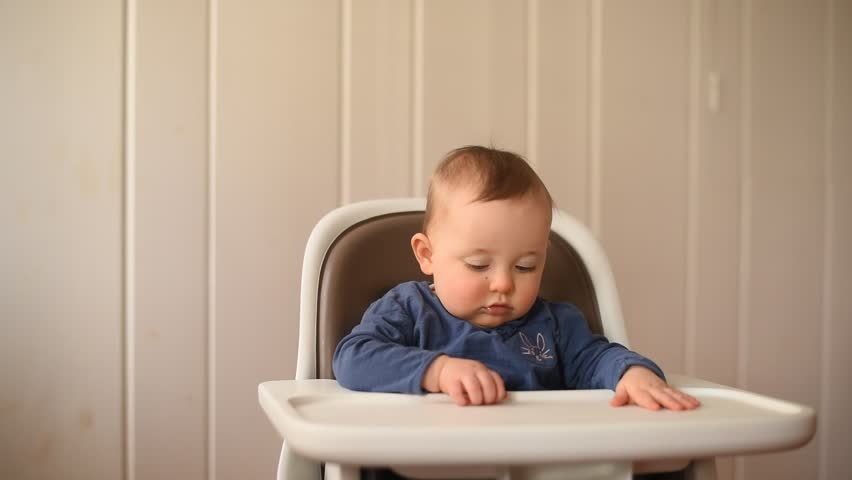 Baby girl sitting in her high chair waving and babbling and eating a cracker.