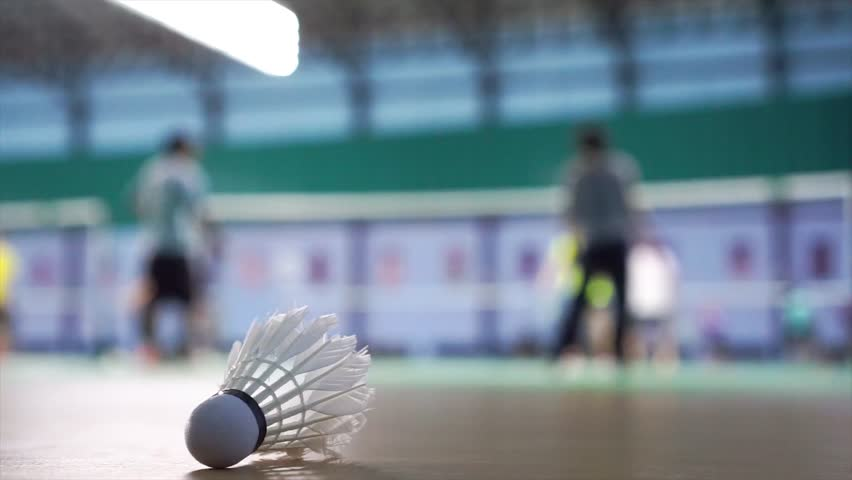 Close up shuttlecocks on racket badminton at badminton courts with players competing