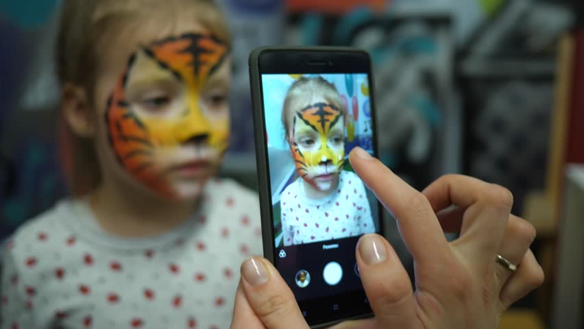 Body art painted face cute little girl on birthday theme party taking phone picture for instagram