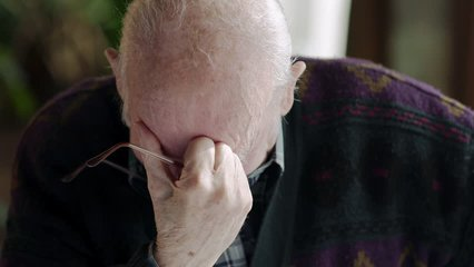 Elderly man overcome with grief sitting with glasses in hand and head bowed before looking up crying.