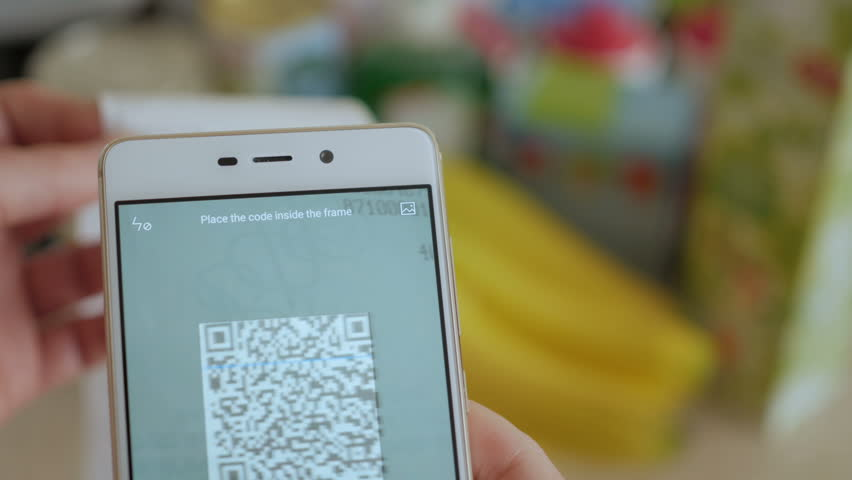 A man scans the QR code on a check from a supermarket.