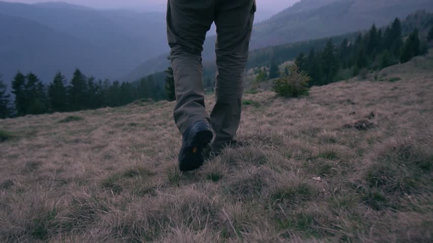 Slow motion:Camera follow hiker's feet on top of the mountain.Close up hiker walking down the valley on sunset.Follow adventurer in magical sunset light on wild mountain.Outdoor activity.Holiday relax