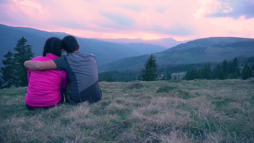 Beautiful couple watching amazing sunset on top of the mountain.Young couple laughing,loving,caress each other while watching beautiful sunset.Cute young lovers hug in sunset light.Outdoor holiday. | Shutterstock HD Video #1009915487