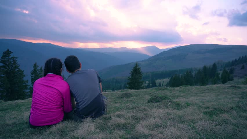 Beautiful couple watching amazing sunset on top of the mountain.Young couple laughing,loving,caress each other while watching beautiful sunset.Cute young lovers hug in sunset light.Outdoor holiday. | Shutterstock HD Video #1009915496
