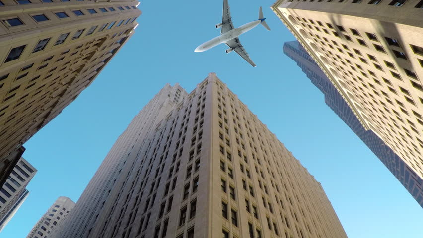 BOTTOM UP, CLOSE UP: Large commercial airplane flies low and close to tall skyscrapers. Breathtaking shot of aeroplane flying over high-rising buildings in business district of metropolitan city. | Shutterstock HD Video #1009915514