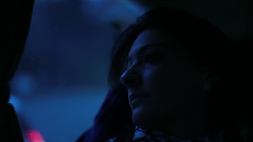 Woman traveling by bus at night
