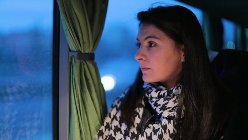 Woman looks out bus window at night while traveling. Girl looking out bus window in the evening