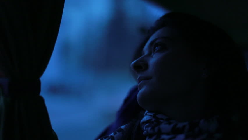 Woman falling asleep while traveling by bus at night. Girl falls asleep next to bus window during evening hours