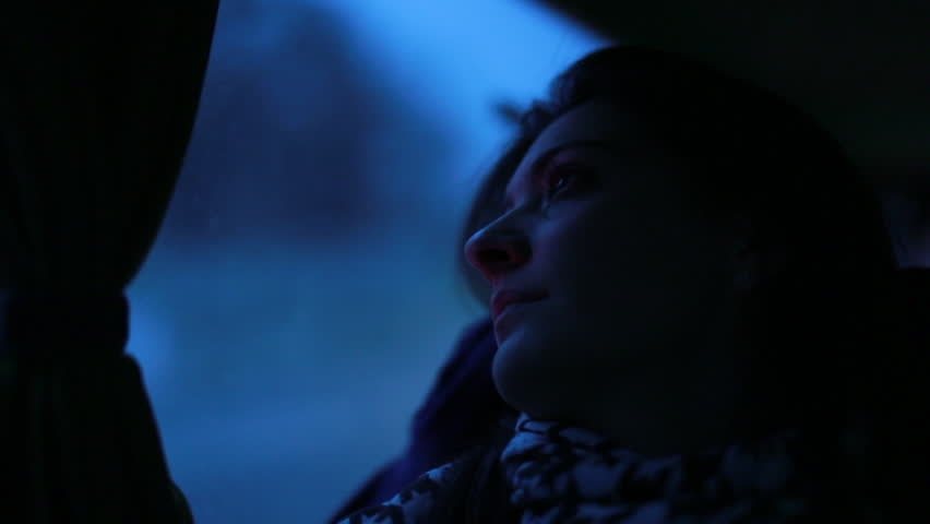 Girl looking out bus window in the evening. Woman looks out bus window at night while traveling during twilight hours